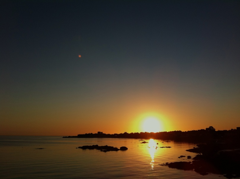 Sun rising over Scotsman's Bay, Sandycove on the first day of winter